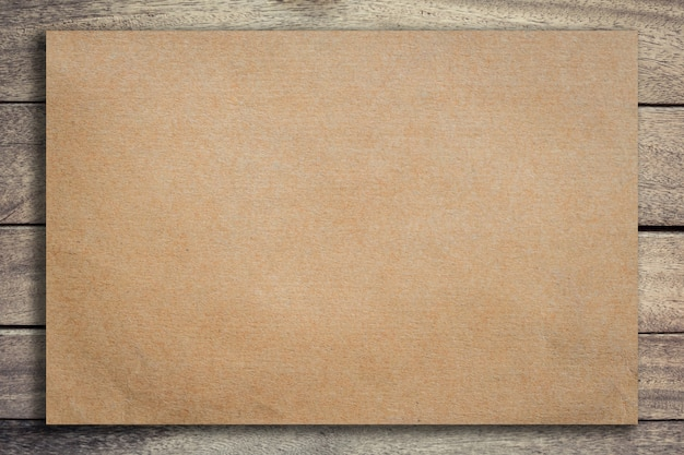 Vecchia carta marrone su sfondo di legno grunge e texture con lo spazio. Foto Premium