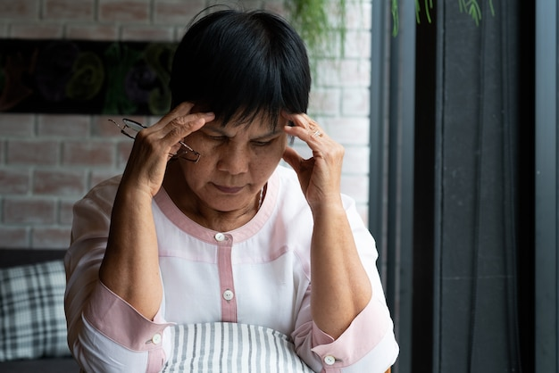 Vecchia donna che soffre di mal di testa, stress, emicrania, problemi di salute Foto Premium