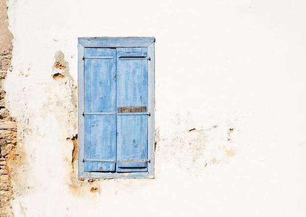 Vecchia finestra in stile mediterraneo. blu su parete chiara con persiane chiuse. Foto Premium