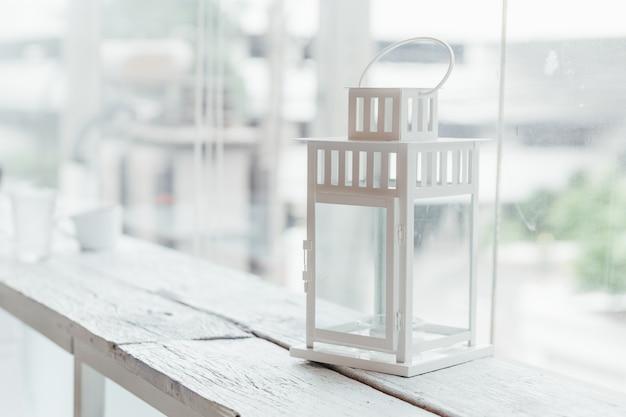 Vecchia lampada bianca sulla tavola di legno dipinta bianca con la finestra di vetro e gli alberi nel fondo. Foto Premium