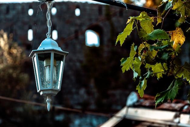 Vecchia lampada d'annata nera sul muro di mattoni con le candele decorative dentro alla vecchia casa di città Foto Premium