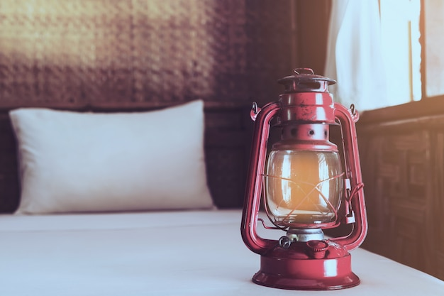Vecchia lanterna sul letto bianco nella località di soggiorno locale natale senza elettricità in tailandia Foto Gratuite