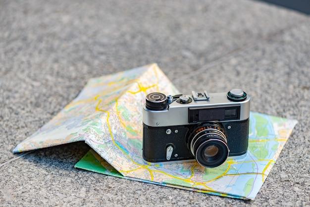 Vecchia macchina fotografica d'annata su un fondo di vecchia mappa che si trova sulla pietra Foto Premium
