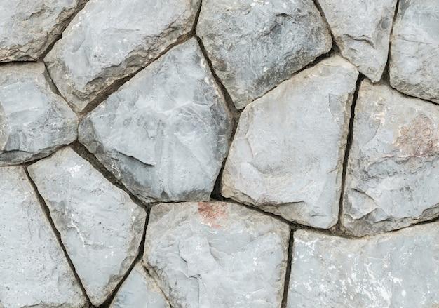 Vecchia parete di pietra del primo piano nei precedenti di struttura del giardino Foto Premium