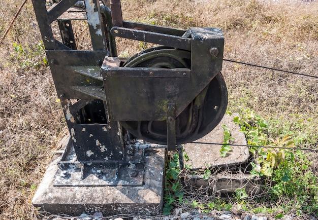 Vecchia puleggia d'acciaio con il filo metallico del palo del segnale stradale. Foto Premium
