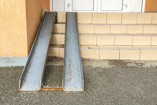 Vecchia rampa di metallo arrugginito per l'ingresso di sedie a rotelle e carrozzina, sopra i gradini. Foto Premium