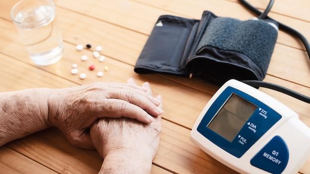 Vecchia signora viene controllata la pressione sanguigna utilizzando il set di bambini monitor di pressione sanguigna Foto Gratuite