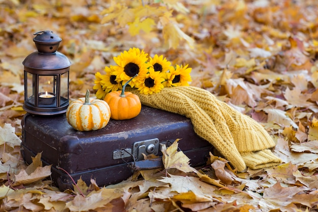 Vecchia valigia, due zucche, una vecchia lanterna con una candela, un mazzo di girasoli e un maglione giallo lavorato a maglia Foto Premium