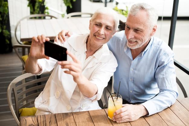 Vecchie coppie del colpo medio che prendono un selfie Foto Gratuite