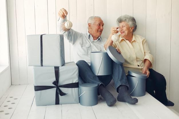 Vecchie coppie eleganti che si siedono a casa con i regali di natale Foto Gratuite