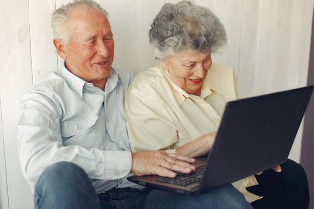 Vecchie coppie eleganti che si siedono a casa e che per mezzo di un computer portatile Foto Gratuite