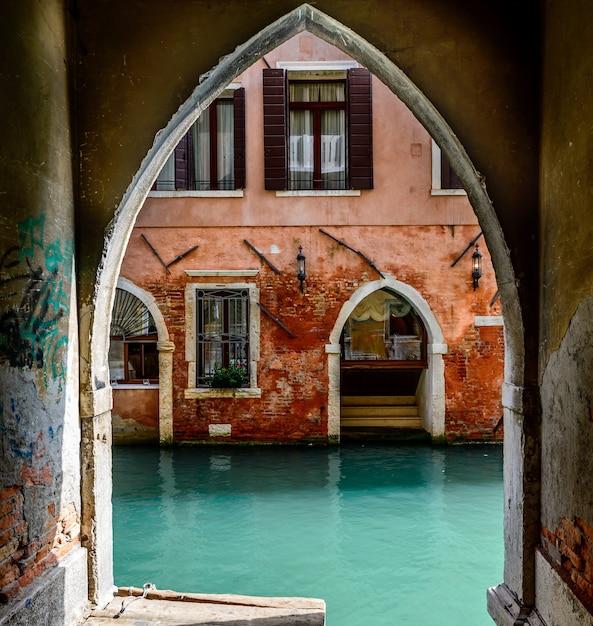 Vecchio arco vicino al canale e un'antica casa rossa con finestre aperte Foto Gratuite