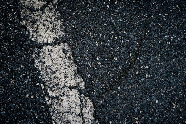 Vecchio asfalto nero con striscia bianca e sfondo di crepe Foto Premium