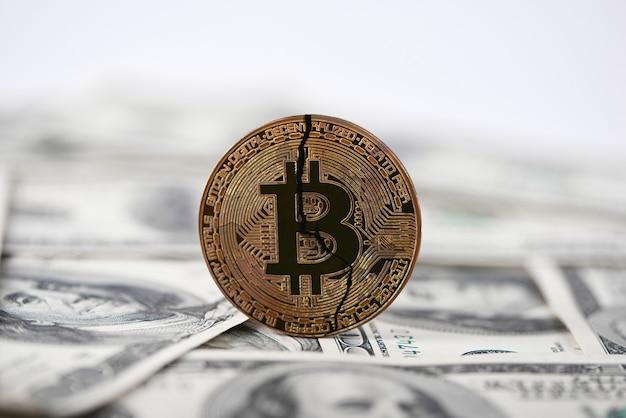 Vecchio bitcoin incrinato sulle banconote del dollaro Foto Premium