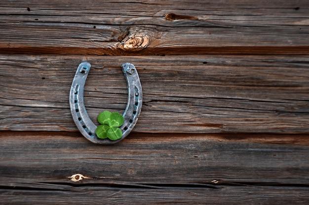 Vecchio ferro di cavallo e quadrifoglio su una tavola di legno d'epoca Foto Premium