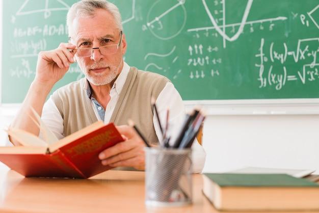 Vecchio insegnante guardando la fotocamera a scuola Foto Gratuite