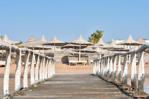 Vecchio molo con una staccionata di legno sulla riva della spiaggia del mare Foto Premium