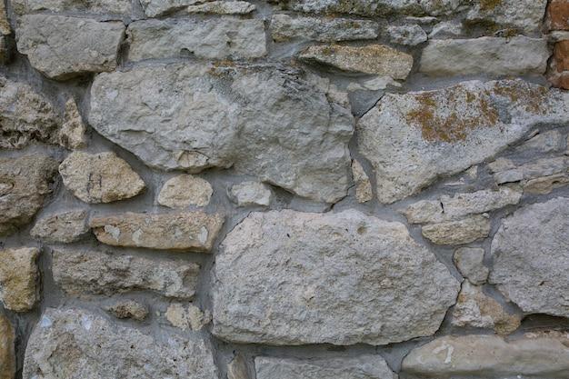 Vecchio muro fatto di grandi pietre e mattoni rotti. priorità bassa di superficie di blocchi grezzi dell'annata Foto Premium
