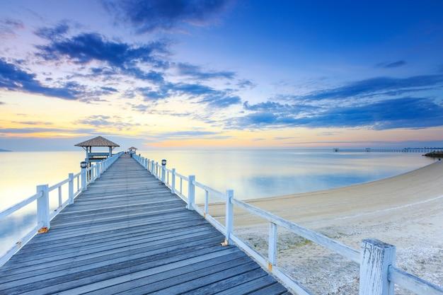 Vecchio pilastro del ponticello di legno contro il bello cielo di tramonto Foto Premium