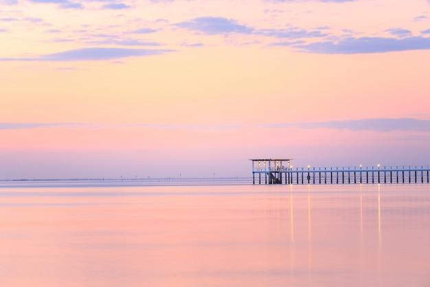 Vecchio pilastro di legno del ponte contro bello uso del cielo di tramonto per sfondo naturale Foto Premium