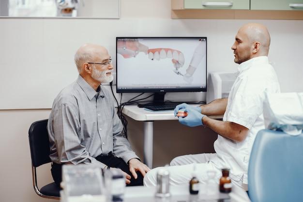 Vecchio seduto nell'ufficio del dentista Foto Gratuite