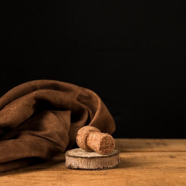 Vecchio sughero e sottobicchiere in legno vicino panno marrone su superficie in legno Foto Gratuite