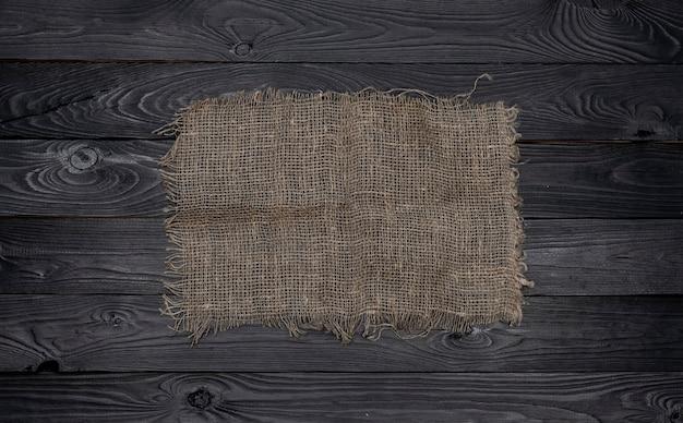 Vecchio tovagliolo del tessuto della tela da imballaggio su fondo di legno nero, vista superiore Foto Premium