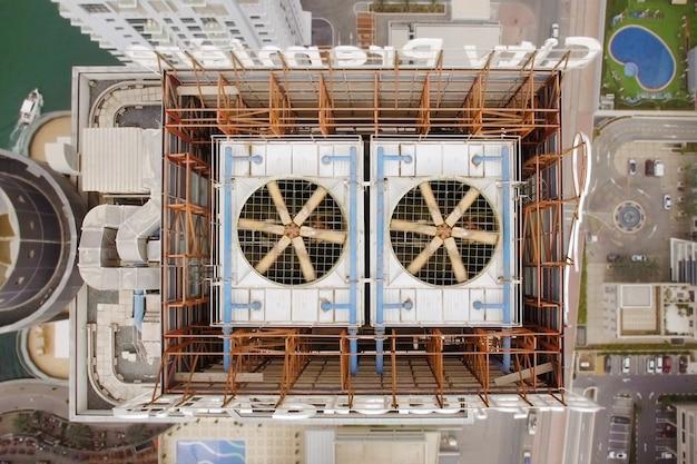 Veduta aerea di due ventole di raffreddamento sul tetto del grattacielo. a sinistra dell'edificio è possibile vedere il lago e alla destra della piscina Foto Premium