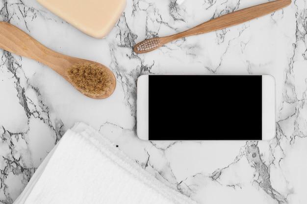 Veduta dall'alto del telefono cellulare; sapone; asciugamano e pennello sullo sfondo di marmo Foto Gratuite