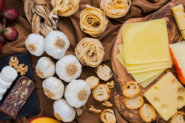 Veduta dall'alto di bulbi di aglio, tipi di formaggio, pasta sul panno marrone Foto Gratuite