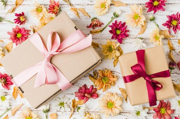 Veduta dall'alto di regali confezionati e vari fiori sulla scrivania ruvida Foto Gratuite
