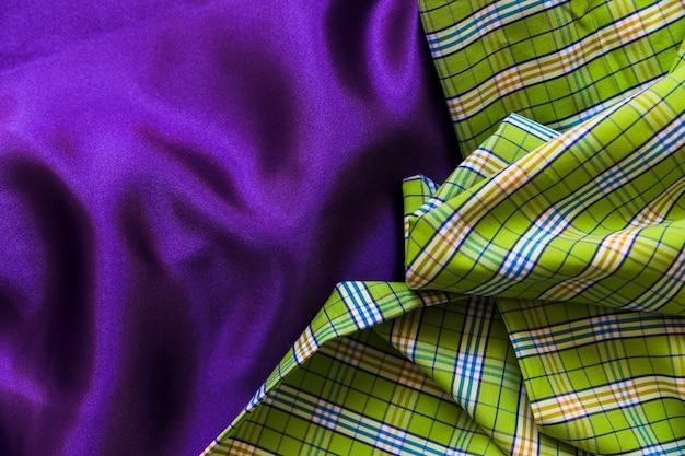 Veduta dall'alto di un panno di cotone scozzese su un semplice tessuto viola Foto Gratuite