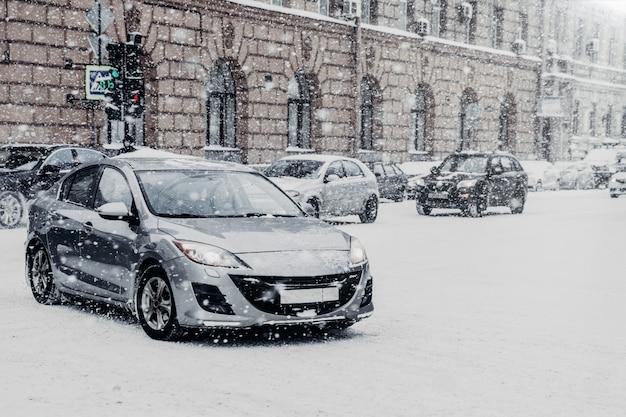 Veicoli coperti di neve durante la bufera di neve invernale. nevicate estreme in città europea Foto Premium