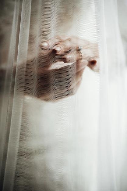 Velo copre le mani della sposa con fedi nuziali Foto Gratuite