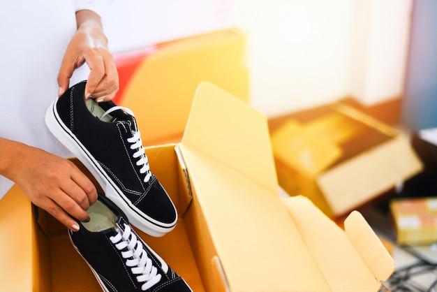Vendita di acquisti online. le scarpe da tennis delle scarpe dell'imballaggio della donna in scatola di cartone preparano la scatola del pacchetto al servizio di consegna. Foto Premium