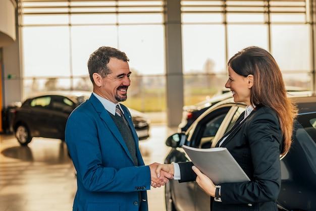 Venditore che stringe le mani con il cliente allo showroom dell'automobile. Foto Premium
