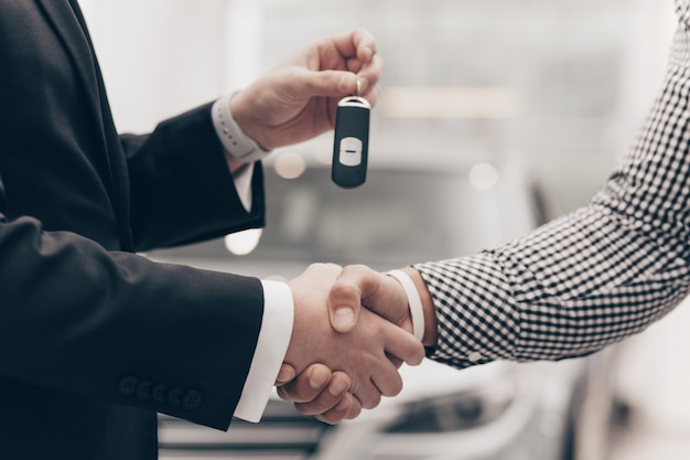Venditore di auto che lavora con un cliente presso il concessionario Foto Premium