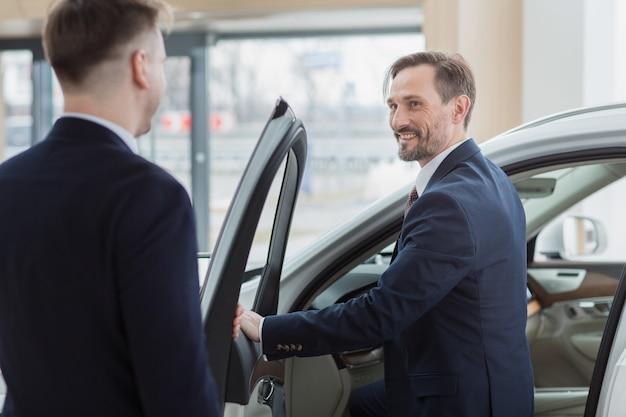 Venditore di auto professionale che aiuta il suo cliente a scegliere una nuova auto Foto Premium