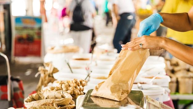 Venditore femminile che pesa alimento in sacco di carta marrone alla stalla del mercato di drogheria Foto Gratuite