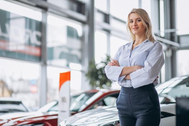 Venditore femminile in una sala d'esposizione dell'automobile Foto Gratuite