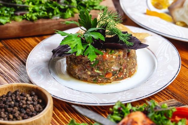 Verdi di pomodoro e pepe nero della cipolla del peperone dolce della melanzana arrostiti insalata laterale di vista sul tavolo Foto Gratuite
