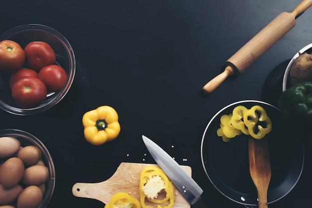 Verdura fresca, uova e peperone a pezzi che taglia a pezzi su fondo di legno nero. Foto Gratuite