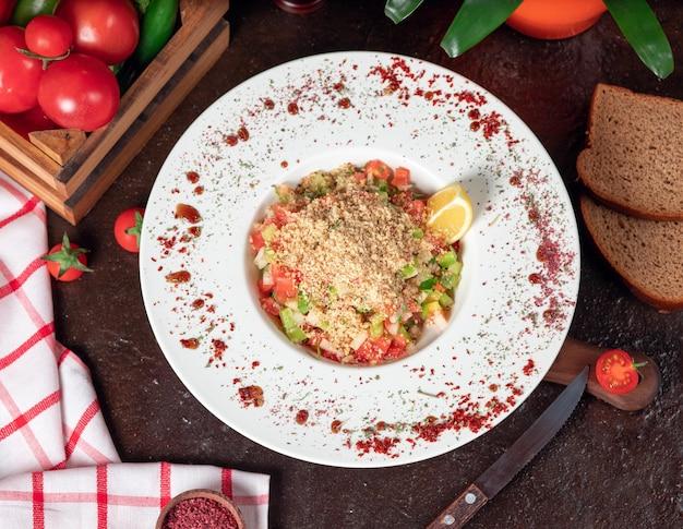Verdura, pomodori, insalata di cetrioli con cracker. insalata sul tavolo della cucina con sumakh e limone all'interno del piatto bianco Foto Gratuite