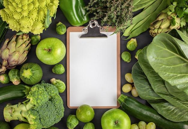 Verdure biologiche verdi e pagina vuota al centro Foto Premium