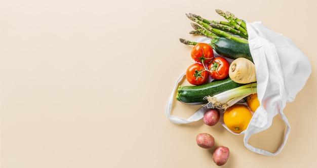 Verdure differenti nella borsa del tessuto su beige Foto Premium