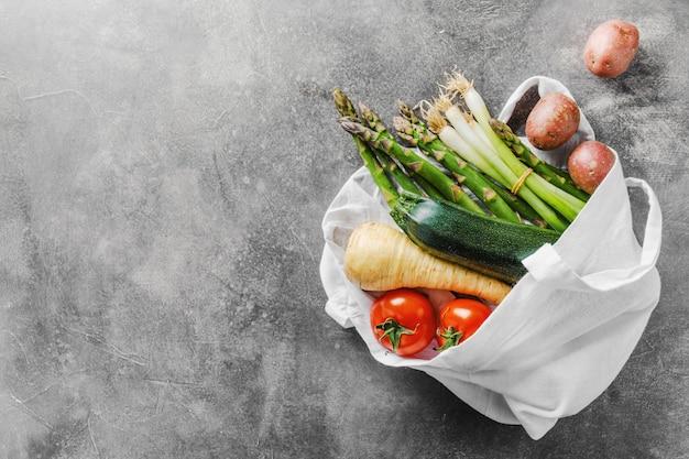 Verdure differenti nella borsa del tessuto su gray Foto Premium