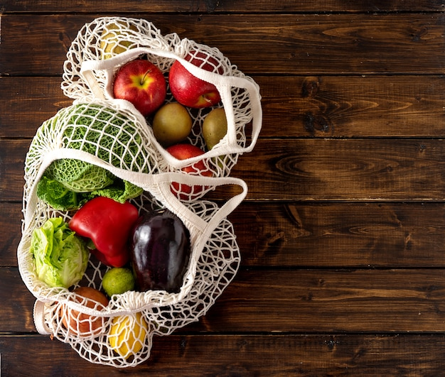 Verdure e frutta in sacchetti netti su fondo rustico scuro Foto Premium