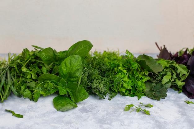 Verdure fresche basilico, coriandolo, lattuga, basilico viola, coriandolo di montagna, aneto, cipolla verde in scatole di plastica su cemento grigio Foto Gratuite