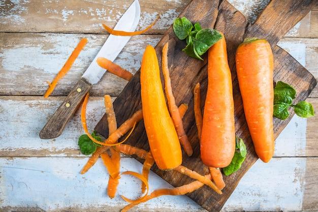 Verdure fresche della carota su una tavola di legno nella cucina Foto Premium