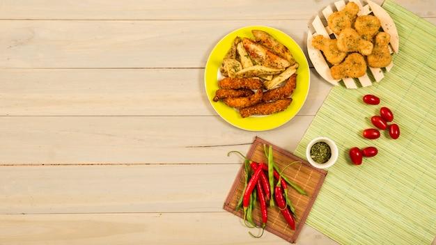 Verdure fresche e spezie vicino pollo arrosto e patate Foto Gratuite